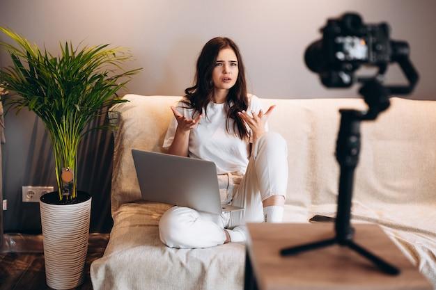 Jovem blogueira surpresa está sentada no sofá com o laptop gravando seu vlog de discurso para o público. blogging indoor.