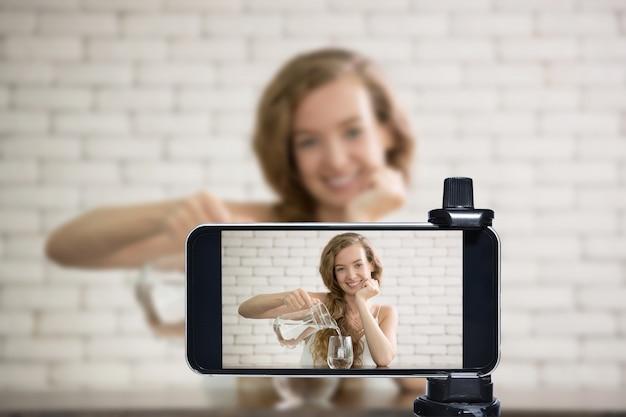 Jovem blogueira, vlogger e influenciadora online transmitem ao vivo um estilo de vida saudável nas mídias sociais usando um smartphone