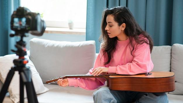 Jovem blogueiro afinando seu violão e gravando a si mesma