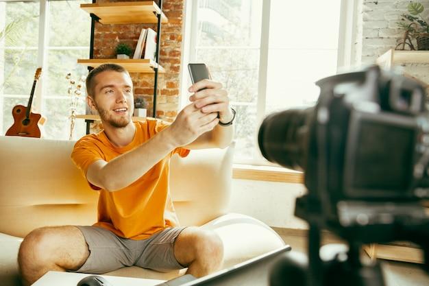 Jovem blogueiro caucasiano com câmera profissional gravando revisão de vídeo de smartphone em casa