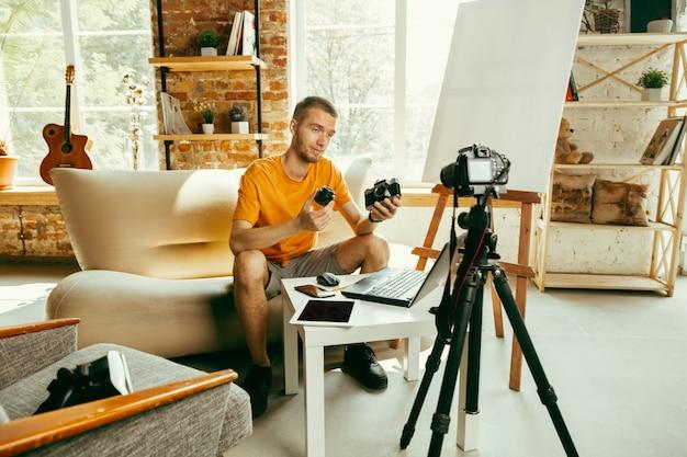 Jovem blogueiro caucasiano com equipamento profissional, gravação de revisão de vídeo da câmera em casa. blogging, videoblog, vlogging. homem fazendo vlog ou transmissão ao vivo sobre fotos ou novidades técnicas.