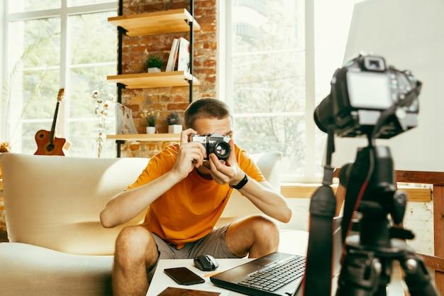 Jovem blogueiro caucasiano com equipamento profissional gravando análise de vídeo da câmera em casa