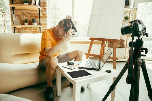 Jovem blogueiro caucasiano com equipamento profissional gravando uma análise de vídeo de óculos de realidade virtual em casa
