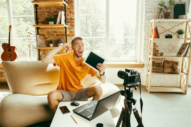 Jovem blogueiro do sexo masculino, caucasiano, com câmera profissional, gravação de revisão de vídeo do tablet em casa. blogging, videoblog, vlogging. homem fazendo vlog ou transmissão ao vivo sobre fotos ou novidades técnicas.