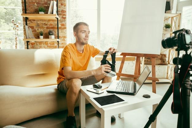 Jovem blogueiro do sexo masculino, caucasiano, com equipamento profissional, gravação de revisão de vídeo de óculos de vr em casa.