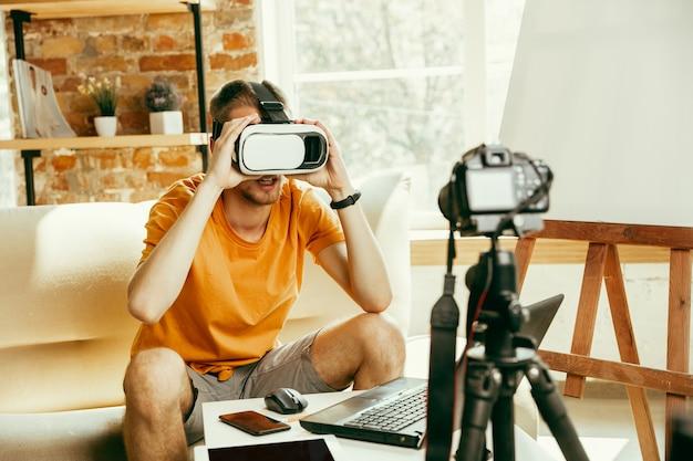 Jovem blogueiro do sexo masculino, caucasiano, com equipamento profissional, gravação de revisão de vídeo de óculos vr em casa blogging, videoblog, vlogging. homem usando fone de ouvido de realidade virtual durante a transmissão ao vivo.