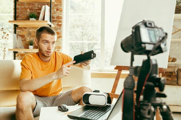 Jovem blogueiro do sexo masculino, caucasiano, com equipamento profissional, gravação de revisão de vídeo de óculos vr em casa blogging, videoblog, vlogging. o homem avalia um fone de ouvido de realidade virtual durante a transmissão ao vivo.