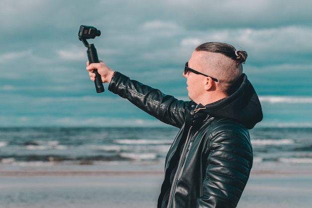 Jovem blogueiro em óculos de sol fazendo selfie ou streaming de vídeo na praia usando câmera de ação com estabilizador de câmera gimbal.