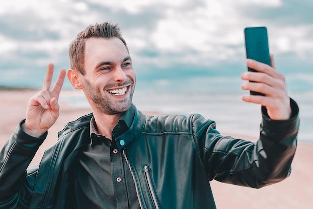 Jovem blogueiro fazendo selfie ou streaming de vídeo na praia usando smartphone preto.