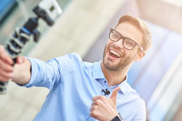 Jovem blogueiro feliz vestindo camisa azul segurando um gimbal com smartphone e gravando