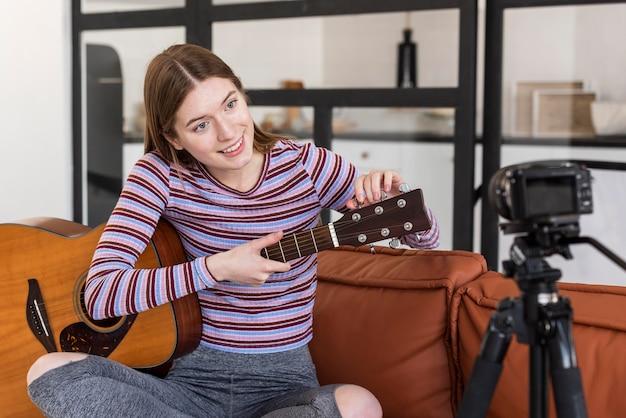 Jovem blogueiro gravando a si mesma e afinando seu violão