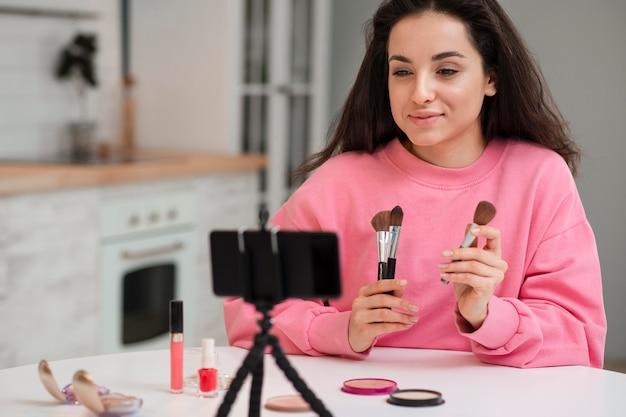 Jovem blogueiro gravando vídeo com acessórios de maquiagem