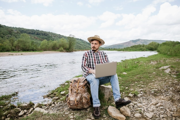 Jovem blogueiro moderno trabalhando remotamente em um laptop ao ar livre enquanto viaja nas montanhas Foto Premium