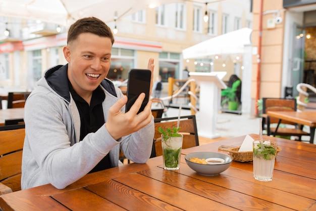 Jovem, blogueiro se senta à mesa de um café de rua e se comunica emocionalmente