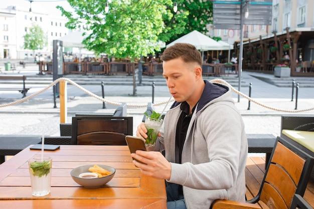 Jovem, blogueiro, sentado à mesa em um café de rua, tira uma selfie no smartphone