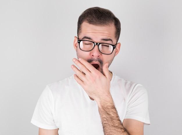 Jovem bocejando de cansaço contra uma parede cinza