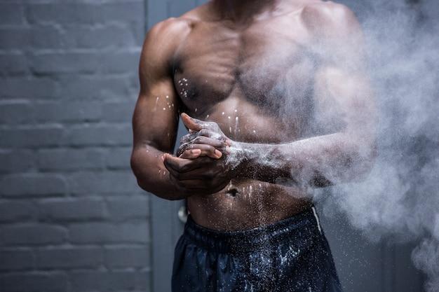 Jovem bodybuilder sacudindo chalk fora de suas mãos