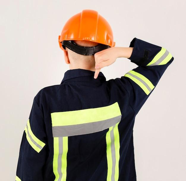 Jovem bombeiro apontando para uniforme