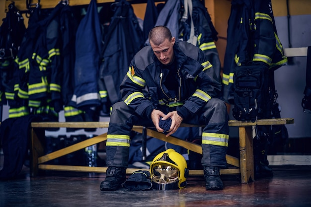Jovem bombeiro atraente em uniforme de proteção sentado no corpo de bombeiros e esperando por outros bombeiros