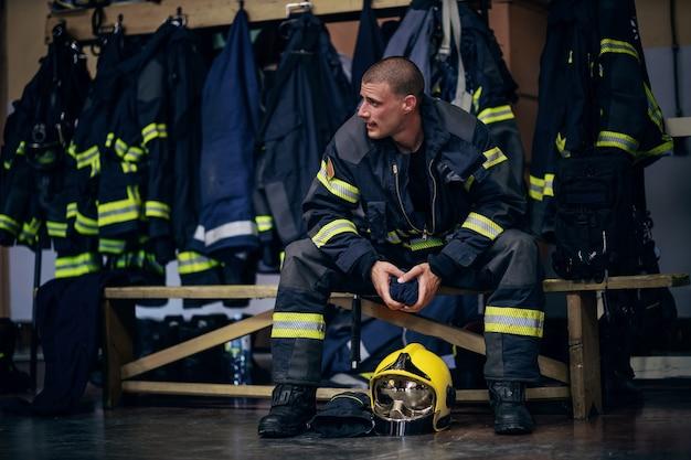 Jovem bombeiro atraente em uniforme protetor sentado no corpo de bombeiros e esperando por outros bombeiros. ele está preparado para a ação.