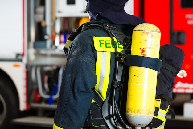 Jovem bombeiro de uniforme na frente do caminhão de bombeiros