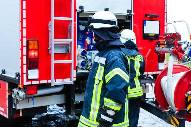 Jovem bombeirouniforme na frente do caminhão de bombeiros