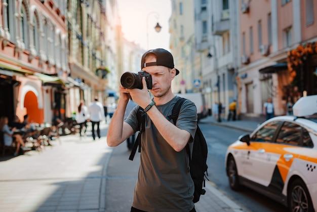 Jovem boné preto, homem com câmera no centro da metrópole tirando fotos