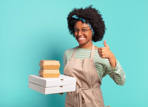 Jovem, bonita, afro, entregadora com caixas de pizza e hambúrgueres para viagem