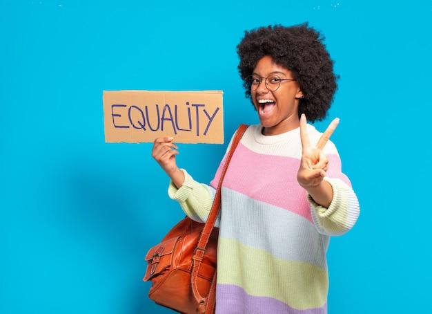 Jovem, bonita, afro, segurando o quadro da igualdade