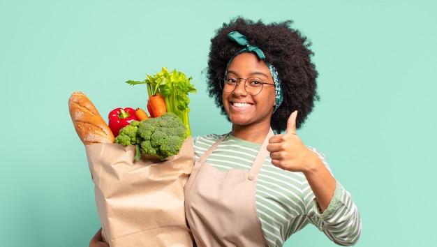 Jovem, bonita, afro, sentindo-se zangada, irritada, irritada, decepcionada ou descontente, mostrando o polegar para baixo com um olhar sério e segurando uma sacola de legumes
