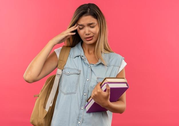 Jovem bonita aluna dolorida vestindo uma bolsa de costas segurando livros e colocando a mão na têmpora, sofrendo de dor de cabeça com os olhos fechados, isolada no rosa com espaço de cópia