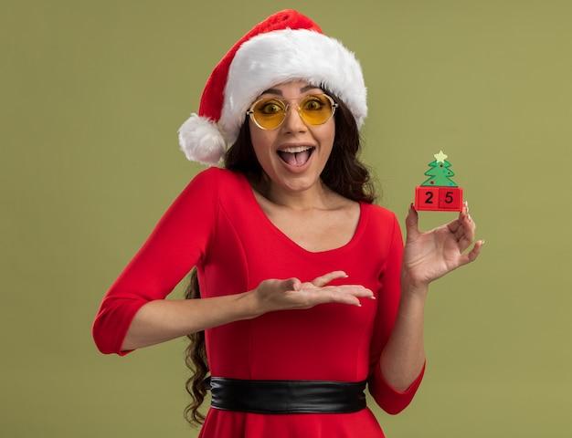 Jovem bonita animada com chapéu de papai noel e óculos, segurando e apontando para o brinquedo da árvore de natal com data isolada na parede verde oliva