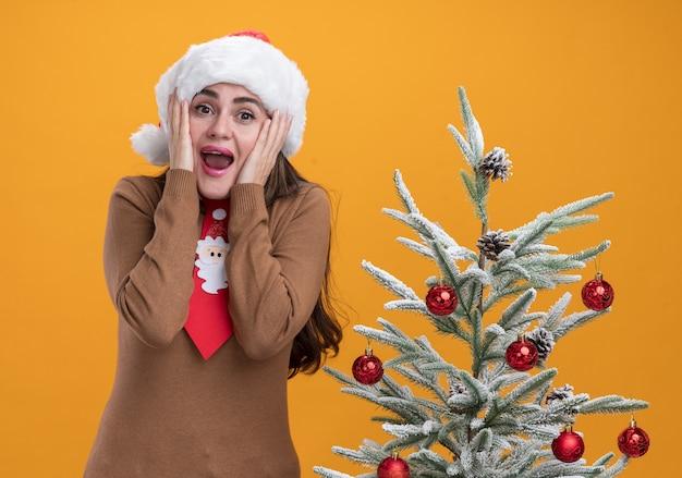 Jovem bonita animada usando chapéu de natal com gravata em pé perto da árvore de natal, colocando as mãos nas bochechas isoladas em fundo laranja