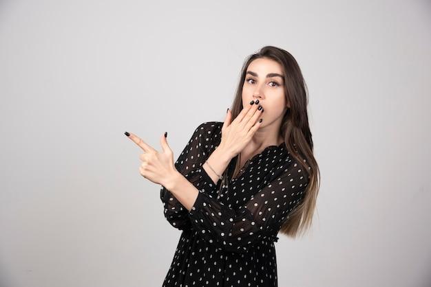 Jovem bonita apontando um dedo em uma parede cinza.