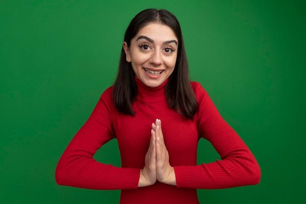 Jovem bonita caucasiana agradecida fazendo gesto de apreciação isolado na parede verde