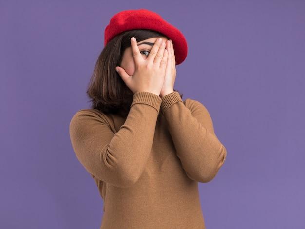 Jovem bonita caucasiana assustada com chapéu de boina cobrindo o rosto com as mãos entre os dedos, isolada na parede roxa com espaço de cópia