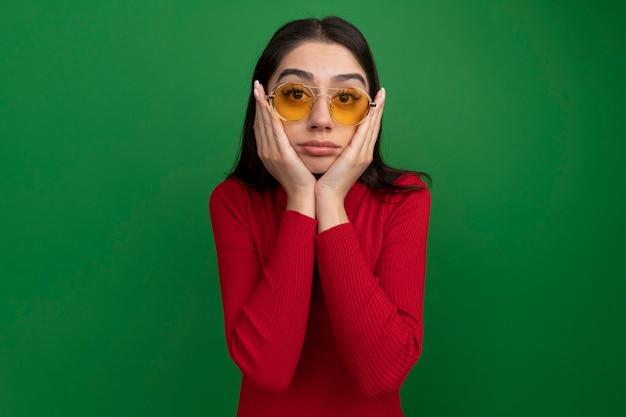 Jovem bonita caucasiana com óculos de sol, mantendo as mãos no rosto isolada em uma parede verde com espaço de cópia