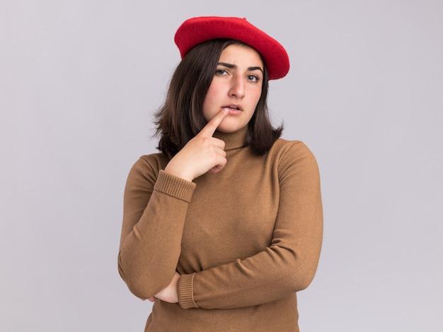 Jovem bonita caucasiana confiante com chapéu boina coloca o dedo na boca olhando para a câmera