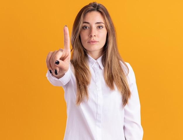 Jovem bonita caucasiana confiante mostrando o dedo indicador