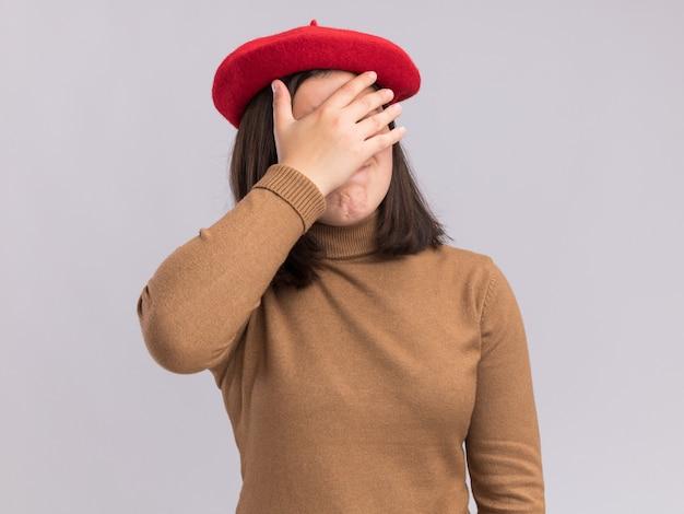 Jovem bonita caucasiana desapontada com chapéu boina cobre o rosto com a mão isolada na parede branca com espaço de cópia