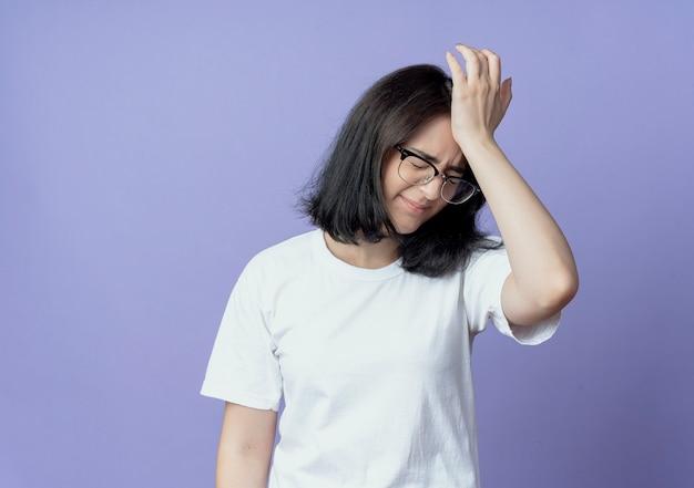 Jovem bonita caucasiana dolorida de óculos, colocando a mão na cabeça, sofrendo de dor de cabeça com os olhos fechados, isolada no fundo roxo com espaço de cópia