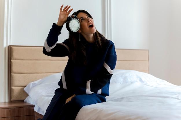 Jovem, bonita, caucasiana, impressionada, sentada na cama no quarto segurando um despertador perto da cabeça, olhando para cima