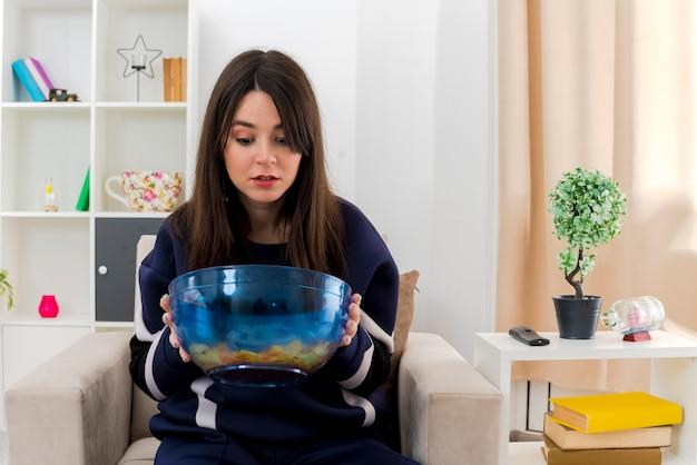 Jovem, bonita, caucasiana, impressionada, sentada na poltrona em uma sala projetada segurando e olhando para dentro da tigela de batatas fritas