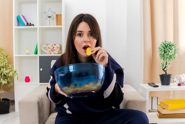 Jovem, bonita, caucasiana, impressionada, sentada na poltrona em uma sala projetada segurando uma tigela de batatas fritas, olhando e comendo batata frita