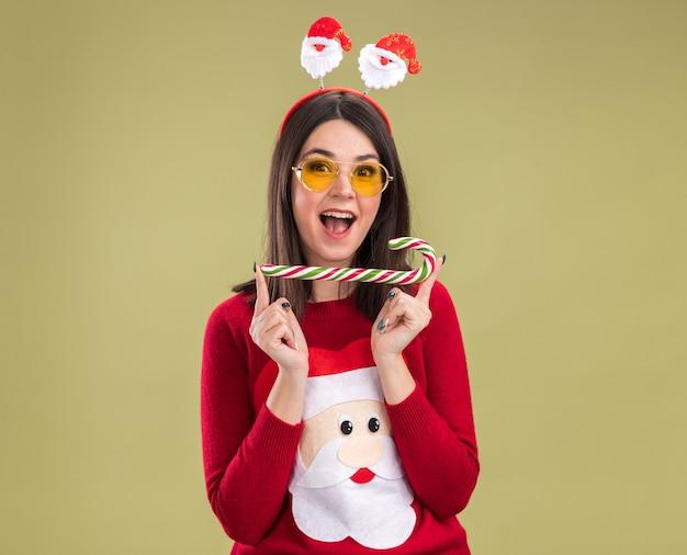 Jovem, bonita, caucasiana, impressionada, vestindo uma blusa de papai noel e bandana com óculos segurando o tradicional bastão de doces de natal horizontalmente