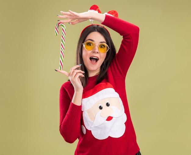 Jovem, bonita, caucasiana, impressionada, vestindo uma blusa de papai noel e bandana com óculos segurando o tradicional bastão de doces de natal na vertical