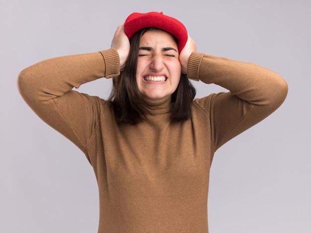 Jovem bonita caucasiana insatisfeita com chapéu boina coloca as mãos na cabeça isolada na parede branca com espaço de cópia