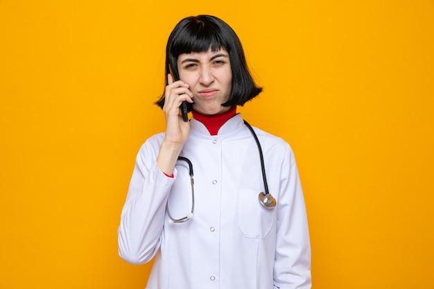 Jovem bonita caucasiana insatisfeita com uniforme de médico e estetoscópio falando ao telefone