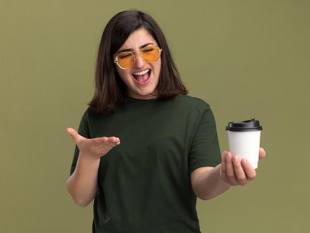 Jovem bonita caucasiana irritada com óculos de sol segura e aponta para o copo de papel na cor verde oliva