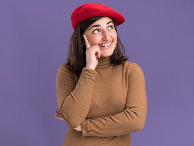 Jovem, bonita, caucasiana, satisfeita, com chapéu de boina coloca a mão na têmpora e olha para o lado isolado na parede roxa com espaço de cópia
